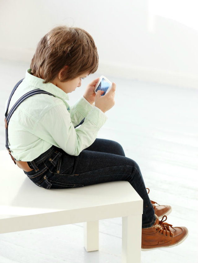 Child sitting on bench with rounded back, hunched shoulders, and poor posture holding a small tablet