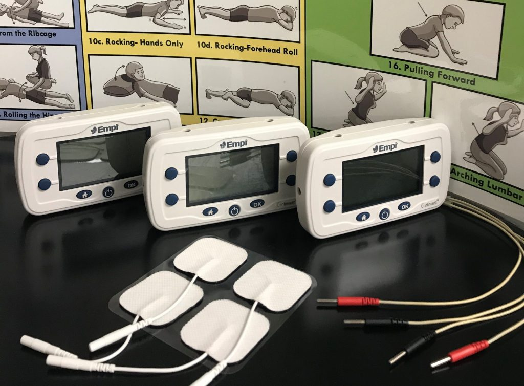 3 Muscle Stim Units stiting on a table with electrodes and wires